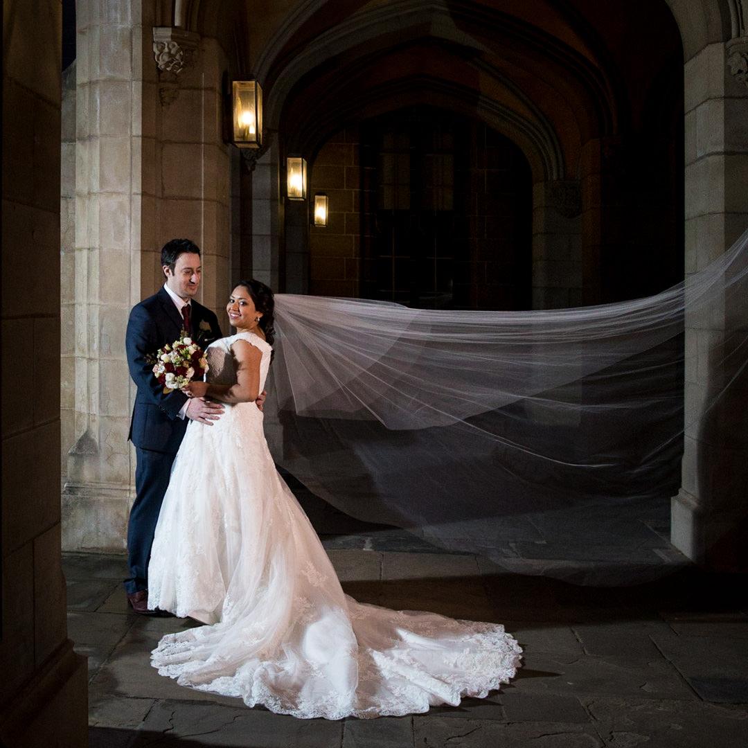 Bride and Groom in corridor with veil flying