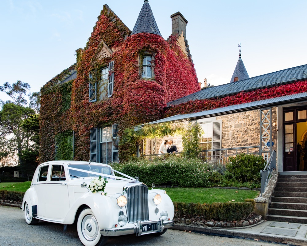 Overnewton Castle - Bride and Groom on porch with car