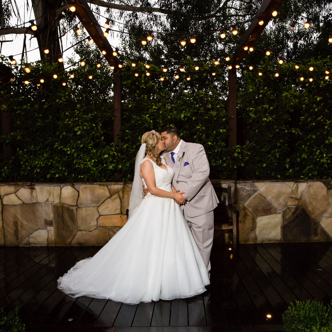 Bride and Groom kissing under fairy lights