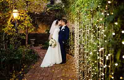 Newlyweds kissing at night time by the fairylights