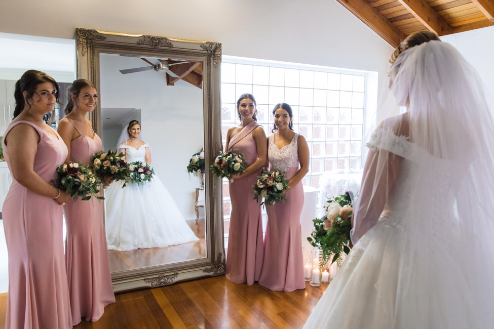 Bride looking in the mirror with bridesmaids